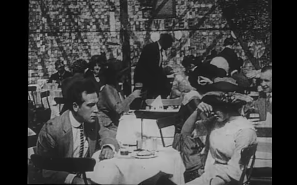 The film image, in black and white, shows a woman with a hat and white dress sitting at a cafe table with a man in a suit. The woman seems to be about to faint and has her hand on her forehead. The man is watching eagerly. The implication is that her drink has been spiked with something.