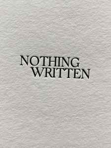 """A textured white piece of paper has two words type-written and centered, in all-caps: """"Nothing Written"""""""